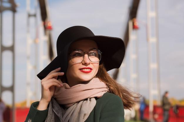 Heureux jeune mannequin avec un maquillage lumineux posant à la ville. femme portant un chapeau, une écharpe et des lunettes à la mode