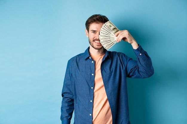 Heureux jeune mec couvrant la moitié du visage avec des dollars et souriant, gagnant de l'argent, debout sur fond bleu.