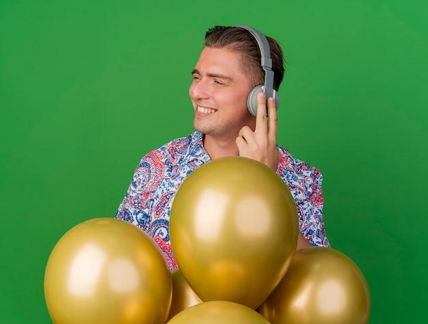 Heureux jeune mec en regardant le côté portant une chemise colorée et des écouteurs debout derrière des ballons isolés sur vert