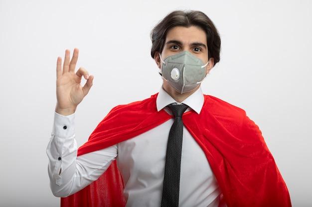 Heureux jeune mec de super-héros portant une cravate et un masque médical montrant un geste correct isolé sur fond blanc