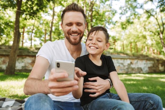 Heureux jeune père assis avec son petit fils à l'aide de téléphone mobile.