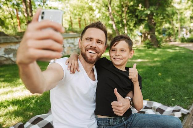 Heureux jeune père assis avec son petit fils faire selfie par téléphone mobile