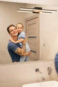 Heureux jeune père célibataire excité avec tatouage sur bras tenant fille d'âge préscolaire et regardant dans le miroir ensemble dans la salle de bains