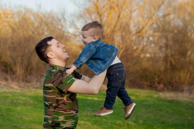 Heureux jeune père jouant avec son fils à l'extérieur