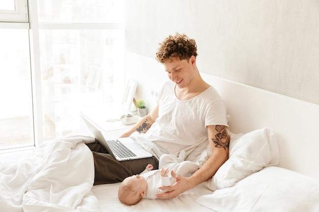 Heureux jeune père jouant avec son petit bébé tout en travaillant sur un ordinateur portable, allongé dans son lit