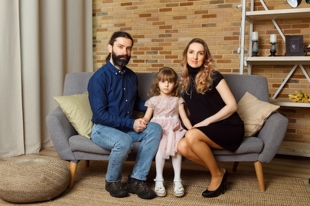 Heureux jeune père, mère et fille assis sur un canapé en osier à la maison. l'image d'une famille heureuse attend le deuxième enfant, studio