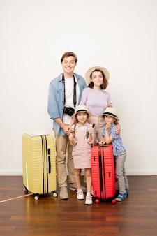 Heureux jeune père, mère, fils et fille occasionnels avec des bagages debout par mur en studio prêt à partir pour le voyage