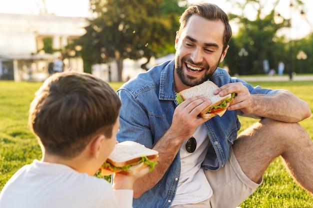 Heureux jeune père pique-niquant avec son petit fils au parc, mangeant des sandwichs