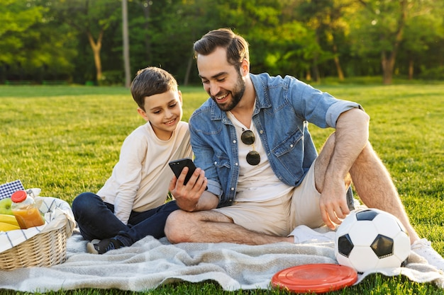 Heureux jeune père pique-niquant avec son petit fils dans le parc, regardant un téléphone portable