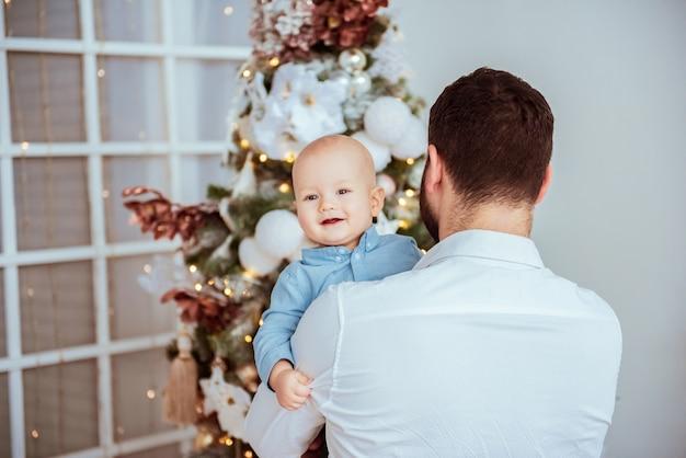Heureux jeune père avec son doux bébé à noël