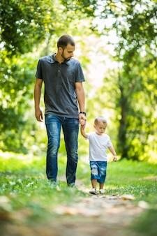 Heureux jeune père tenant son petit fils à la main et marchant sur le parc