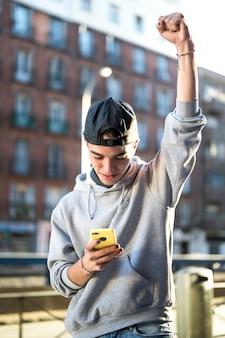 Heureux jeune regardant le téléphone excité par de bonnes nouvelles en ligne
