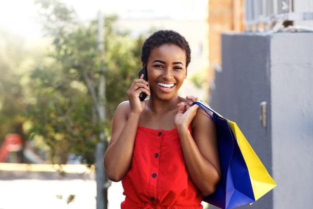 Heureux jeune avec des sacs à provisions femme parlant au téléphone