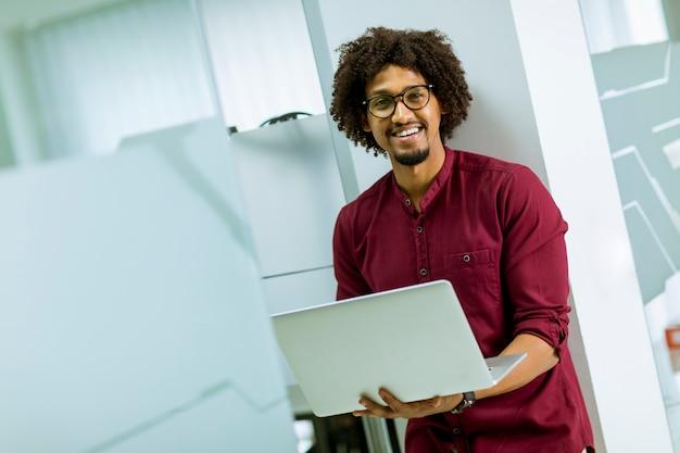 Heureux jeune spécialiste américain en informatique, portant des lunettes, travaillant sur son ordinateur portable au bureau