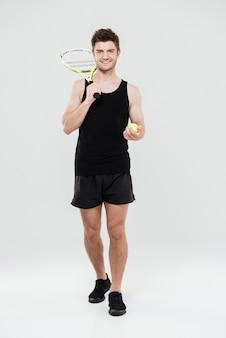 Heureux jeune sportif tenant une balle de tennis et une raquette.