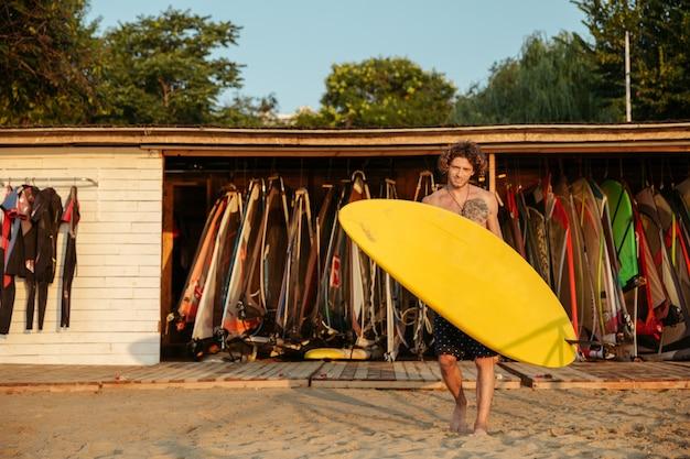 Heureux jeune surfeur bouclé avec planche de surf jaune marchant sur la plage