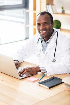 Heureux jeune travailleur médical en uniforme tout en utilisant son ordinateur