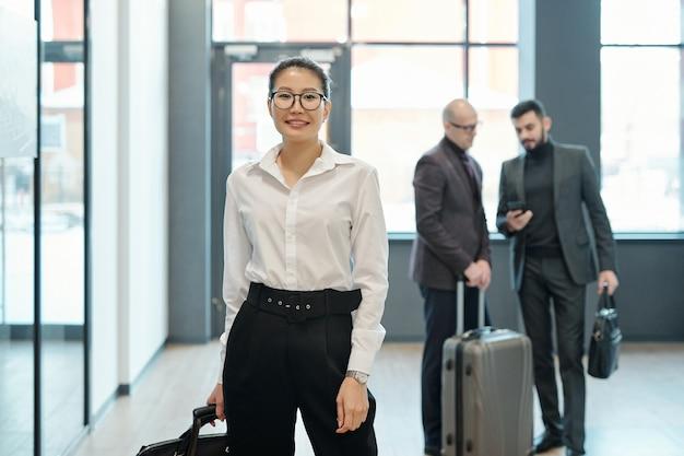 Heureux jeune voyageur d'affaires féminin réussi avec des bagages