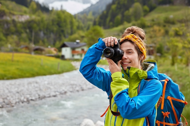 Heureux jeune voyageur féminin fait une photo de paysage de montagne et de rivière
