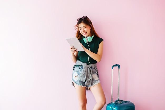 Heureux jeune voyageur femme avec valise et casque de musique à l'aide de tablette et souriant