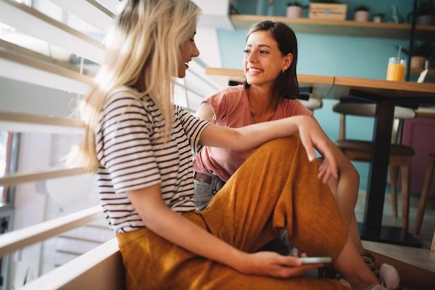 Heureux jeunes amis belles femmes s'amusant, parlant et souriant