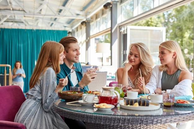 Heureux jeunes amis caucasiens réunis au café