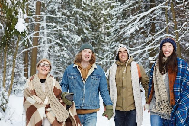 Heureux jeunes amis dans la forêt d'hiver