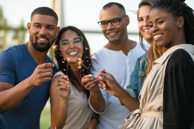 Heureux jeunes amis avec des feux de bengale