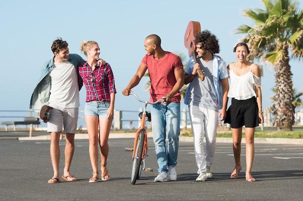 Heureux jeunes amis marchant dans une rangée