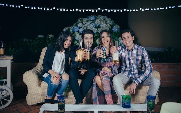 Heureux jeunes amis riant et montrant des boissons lors d'une fête en plein air. concept d'amitié et de célébrations.