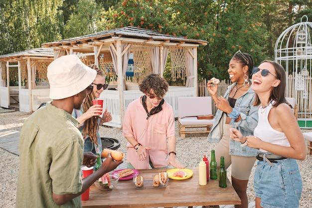 Heureux jeunes amis s'amusant par table avec des collations