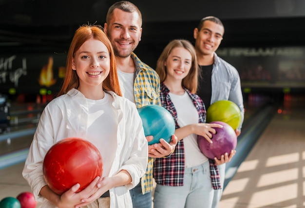Heureux jeunes amis tenant des boules de bowling coup moyen