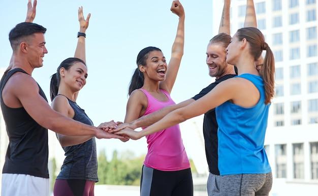 Heureux jeunes athlètes tenant les mains droites empilés