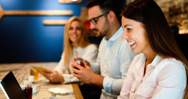 Heureux jeunes collègues du travail socialisant au restaurant