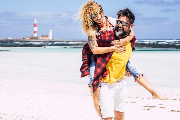 Heureux jeunes couples adultes jouent et profitent ensemble des vacances d'été