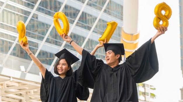 Heureux jeunes diplômés assis avec les robes de graduation en cérémonie de félicitation avec ballon 2018.