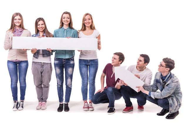 Heureux jeunes étudiants souriant et tenant une table blanche.