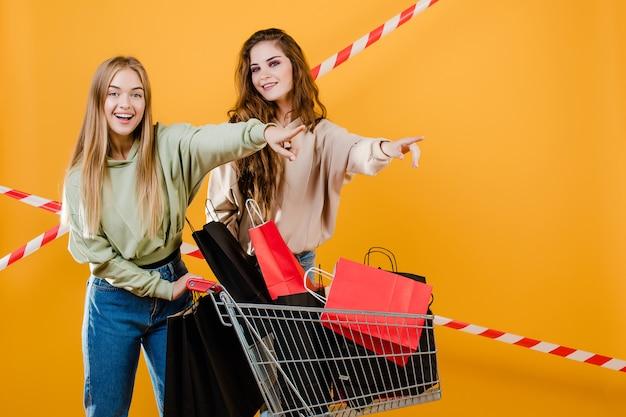 Heureux jeunes femmes montrant du doigt la surface avec un chariot rempli de sacs à provisions et de ruban de signalisation isolé sur jaune