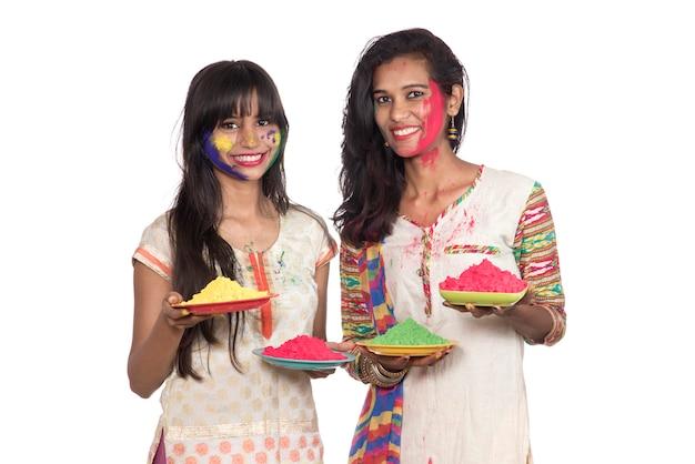 Heureux jeunes filles s'amusant avec de la poudre colorée au festival holi de couleurs