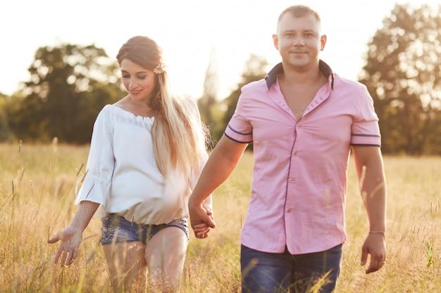 Heureux les jeunes futurs parents se promènent dans le pré vert, se tiennent la main, profitent d'une atmosphère calme, ont des expressions heureuses, anticipent pour bébé. concept de personnes, famille, relation et grossesse
