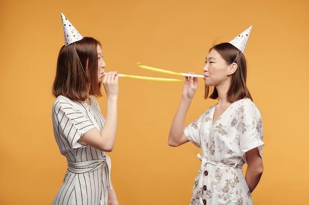 Heureux jeunes jumeaux magnifiques dans des robes élégantes et des casquettes d'anniversaire se tenant les uns devant les autres et sifflant sur fond jaune