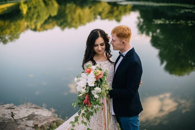 Heureux jeunes mariés debout sur la rive du fleuve