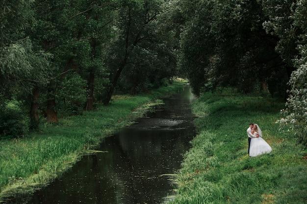Heureux jeunes mariés à l'extérieur près de la rivière. mariée et le marié s'embrasser en plein air sur le parc verdoyant