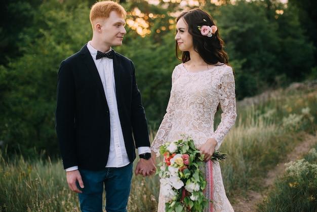 Heureux jeunes mariés se tenant la main et marchant dans la nature