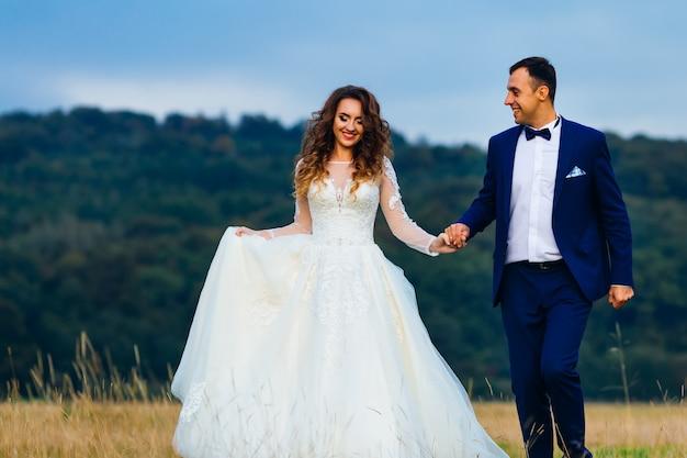 Heureux jeunes mariés se tiennent la main et marchent près de la forêt