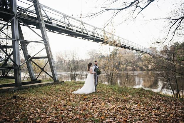 Heureux jeunes mariés souriants se tiennent près du pont suspendu et de la rivière. photos de mariage dans un endroit intéressant