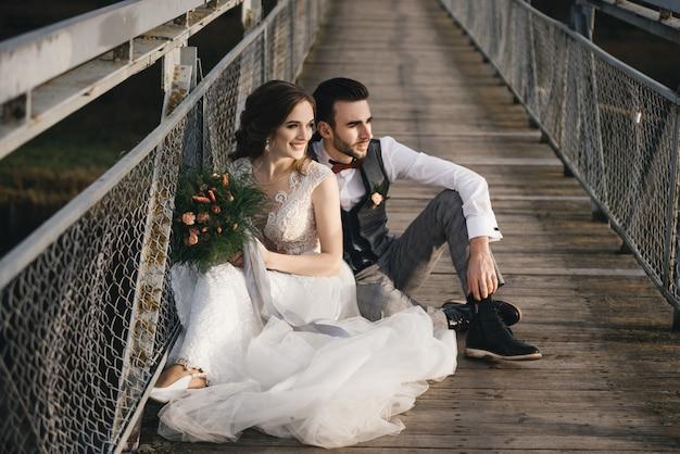 Heureux jeunes mariés souriants sont assis sur le pont suspendu. photos de mariage ensoleillées dans un endroit intéressant