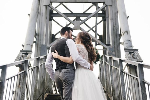 Heureux jeunes mariés souriants sont debout sur le pont suspendu. photos de mariage dans un endroit intéressant