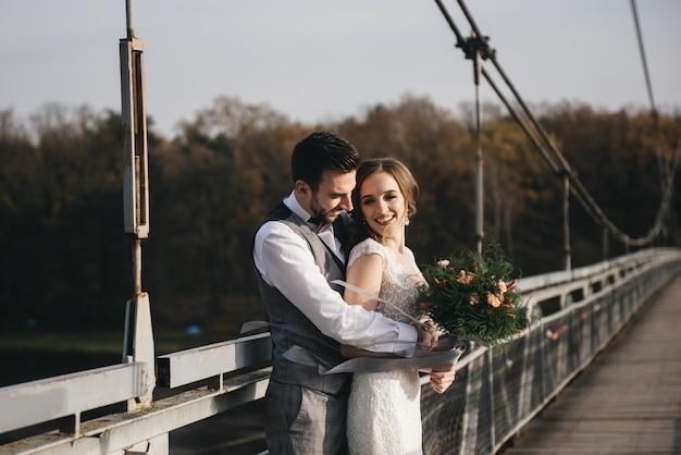Heureux jeunes mariés souriants sont debout sur le pont suspendu.