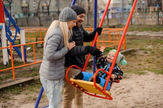 Heureux jeunes parents balançant un fils d'enfant en bas âge sur une balançoire